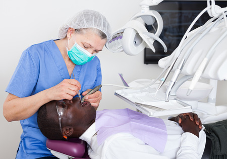 Dentist professional filling teeth for man patient sitting in medical chair Фото со стока