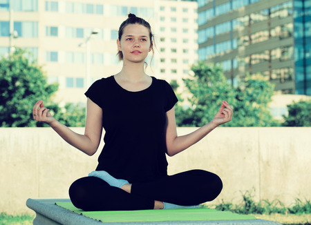 Sporty young female meditating in yoga position Padmasana outdoors Stock Photo