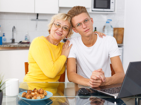 Portrait of loving mother and her adult son at kitchen
