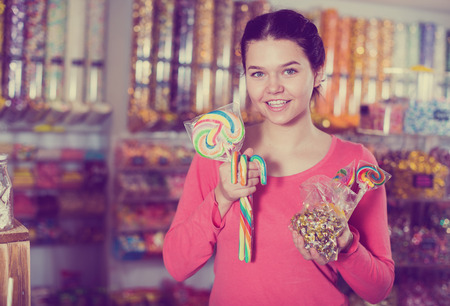 Happy brunette girl buying candies at shop Фото со стока - 120865342
