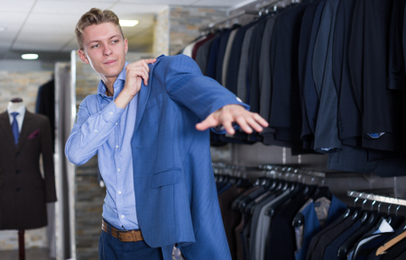 Man purchaser in business suit trying jacket in the dress shop