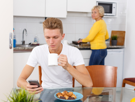 Young guy sitting at kitchen while his mature mother cooking breakfast