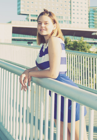 Young positive girl in blue dress standing on modern city bridge 스톡 콘텐츠