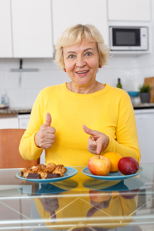 Senior lady demonstrating advantage of healthy food and choosing fruits Imagens