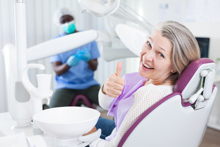 Happy cute mature woman sitting in dental chair after teeth cure giving thumb up Archivio Fotografico