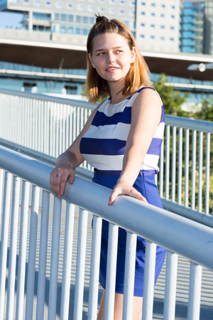 Portrait of young stylish girl posing on city bridge in summer day