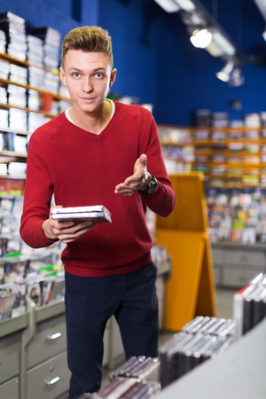 Positive guy standing near shelves with CD and DVD in shop, holding out CD case to somebody Фото со стока - 120856223