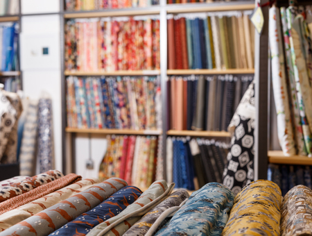 Rolls of fabric and textiles for sale stacked on shelves in shop