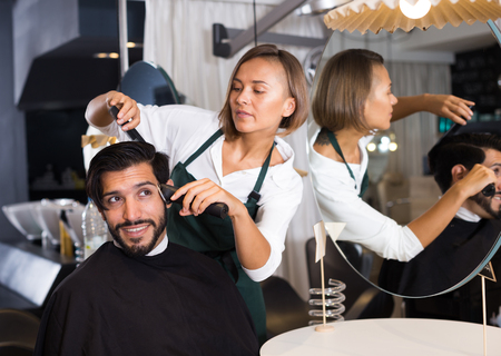 female professional shaving cheerful male's hair in hairdressing salon Banque d'images
