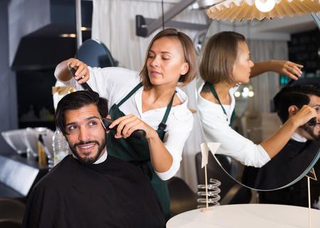 female professional shaving cheerful male's hair in hairdressing salon 版權商用圖片