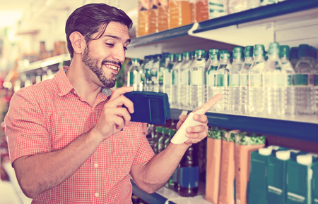 happy european man is choosing water using note list and a call to his wife in supermarket.