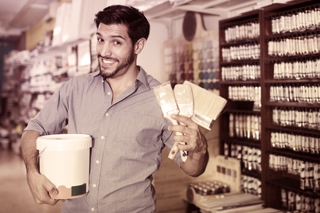 Positive male buyer holding bucket of paint and brushes in paint shop