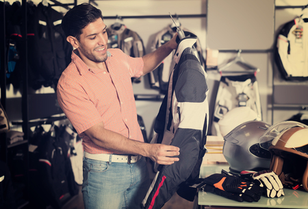 Happy man is choosing new jacket for motorbike in the store