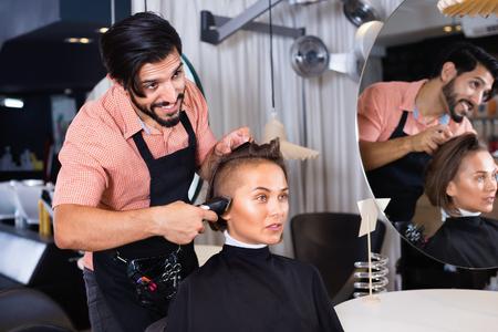 Retrato de peluquería hombre positivo alegre cortando el cabello de la mujer en el salón