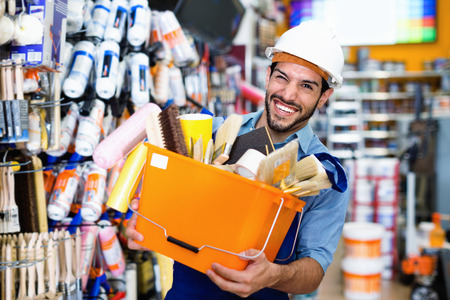 Smiling workman holding basket with picked tools in paint store