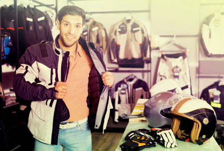 Active man is trying up new jacket for motorbike in the store