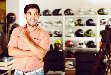 Retrato de cliente masculino sonriente contento que está posando en la tienda de moto.