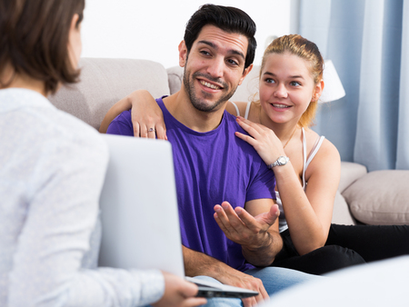 Young smiling couple consulting with female real estate agent in home interior