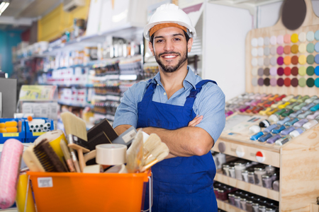 Young master satisfied with purchases in paint store standing near basket with picked tools
