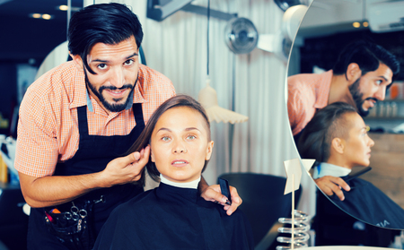 adult positive male hairdresser and female client in beauty salon