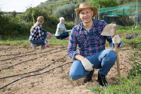 Portrait of male farmer with hoe during work with family in vegetable garden in springtime