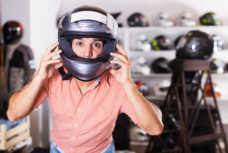 Adult man is trying up new helmet for head protection in the moto shop Stock Photo