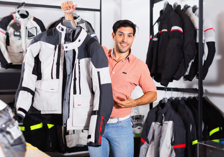 Glad cheerful  male customer is demonstrating modern jacket that he choose in the sport store.
