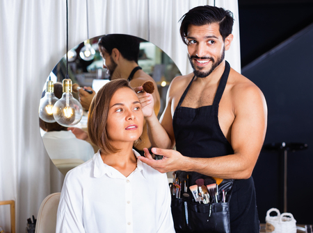 Happy cheerful positive   man makeup artist applying cosmetics for woman