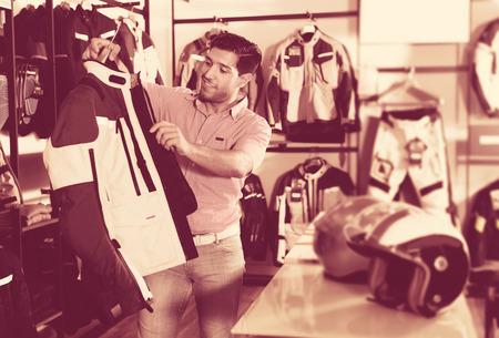 Male customer is choosing modern jacket in the sport store. 版權商用圖片