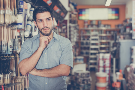 Thoughtful serious young man standing amongst racks with tools in hardware store