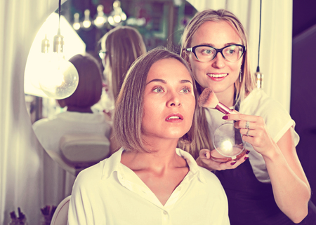 Cheerful positive  woman makeup artist applying cosmetics for female