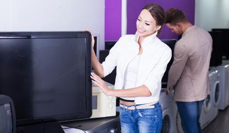 Young woman choosing TV set
