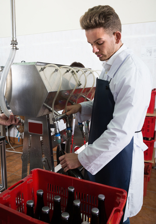 Man employee using machine to bottle wine at sparkling wine industry