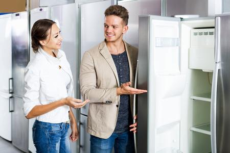 Glad middle class family couple choosing new refrigerator in supermarket Reklamní fotografie
