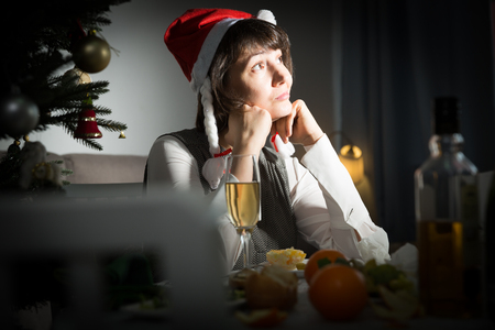 Sad bored adult woman watching Christmas tv program sitting alone at table with wine glass in dark room