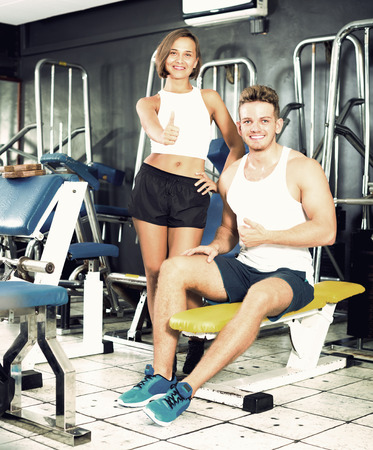 young joyful smiling man and woman fitness coaches taking break during workout in gym indoors. Focus on man