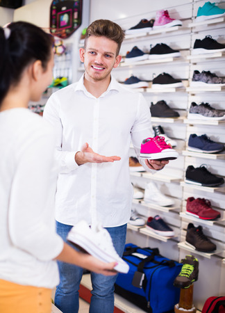 Young male seller demonstrating sneakers to female customer in sports store