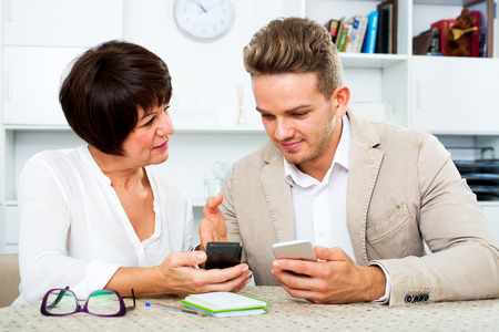 Happy elderly mother with her young son studing new functions of smartphones