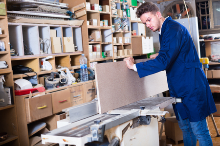 Young male carpenter adjusting chipboard at workplace