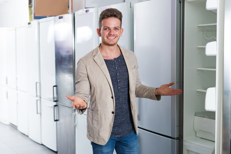 Ordinary male customer looking at modern fridges in hypermarket