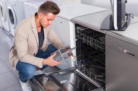 Client masculin regardant les lave-vaisselle dans le magasin d'appareils électroménagers à l'intérieur