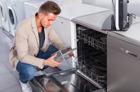 Male customer looking at dishwashers in domestic appliances store indoors