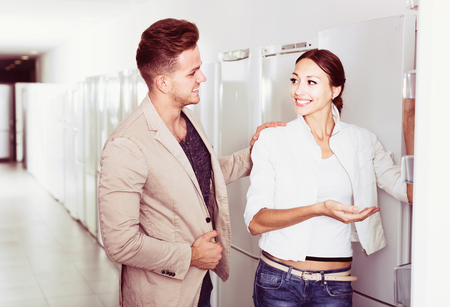 Happy young customers looking at fridges in domestic appliances store Stock Photo