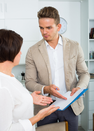 Young man tries to persuade elderly woman to sign documents Stock Photo