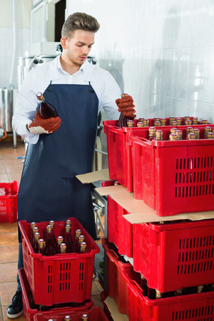 Glad cheerful male worker packaging wine bottles at sparkling wine factory