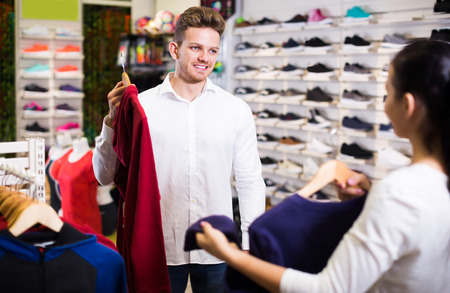Smiling loving couple deciding on new sportswear in sports store
