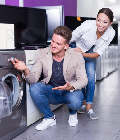 Smiling  family couple selecting new clothes washer in store