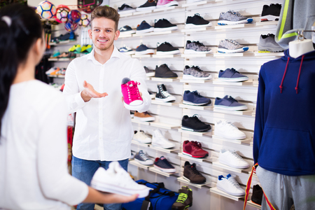 Male seller demonstrating sneakers to female customer in sports store Stock Photo