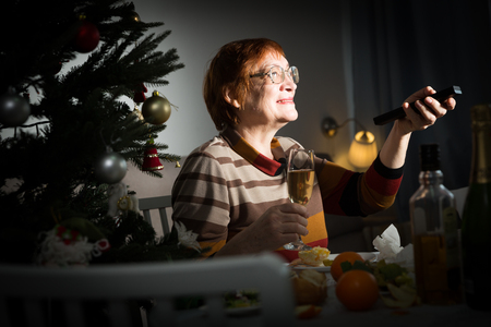Senior woman with remote control in hand watching TV on New Year night