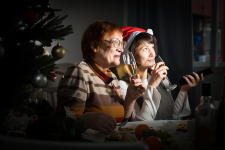 Portrait of female friends in festive mood during Christmas holiday watching tv in dark room